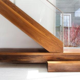 Imagen de escalera en L, minimalista, sin contrahuella, con escalones de madera y barandilla de vidrio