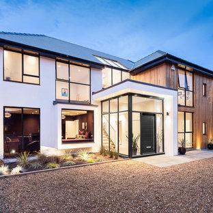 Diseño de escalera recta, moderna, de tamaño medio, con escalones de madera, contrahuellas de madera y barandilla de vidrio