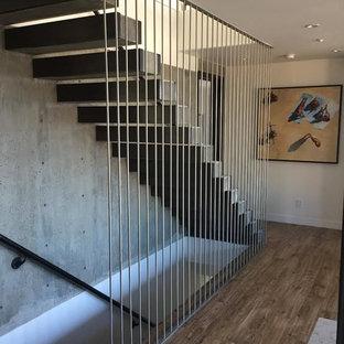 Idee per una grande scala a rampa dritta minimalista con pedata in legno, parapetto in cavi e nessuna alzata