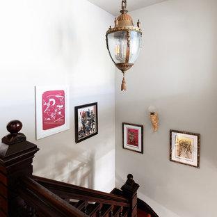 Ejemplo de escalera en L, ecléctica, de tamaño medio, con escalones enmoquetados, contrahuellas enmoquetadas y barandilla de madera