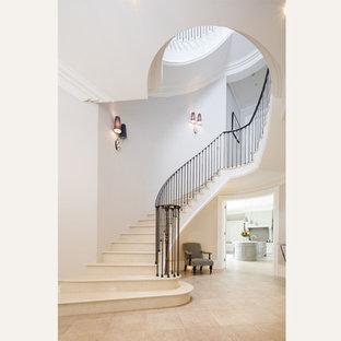 Diseño de escalera curva, tradicional, grande, con escalones con baldosas, contrahuellas con baldosas y/o azulejos y barandilla de varios materiales