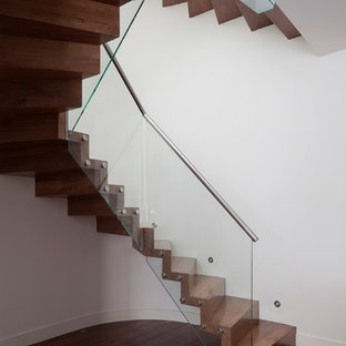 Minimalist wooden curved staircase photo in London with glass risers