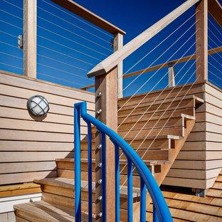 Imagen de escalera en L, costera, pequeña, con escalones de madera, contrahuellas de madera y barandilla de metal
