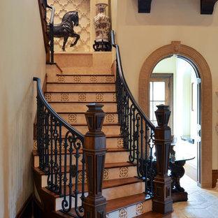 Imagen de escalera curva, clásica, de tamaño medio, con escalones de madera y contrahuellas con baldosas y/o azulejos