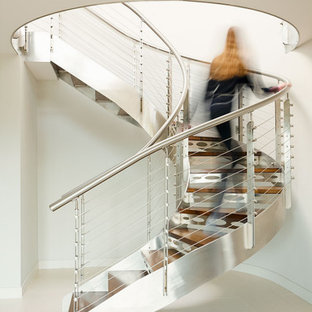 Design ideas for an expansive industrial wood curved metal railing staircase in Cornwall with metal risers.
