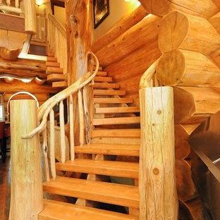 Diseño de escalera curva, rústica, de tamaño medio, con escalones de madera y barandilla de madera