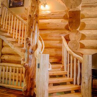 Idee per una scala curva stile rurale di medie dimensioni con pedata in legno e parapetto in legno