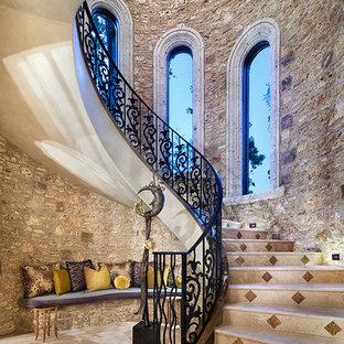 Exempel på en stor medelhavsstil svängd trappa i marmor, med räcke i metall och sättsteg i marmor
