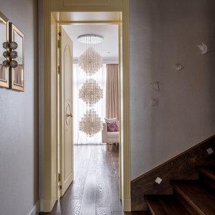На фото: п-образная лестница среднего размера в стиле фьюжн с деревянными подступенками, деревянными перилами и обоями на стенах с