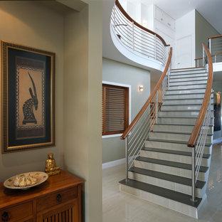 ケアンズの大きいタイルのモダンスタイルのおしゃれなサーキュラー階段 (タイルの蹴込み板、混合材の手すり) の写真