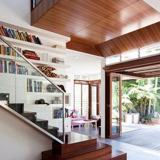 Immagine di una grande scala tropicale con pedata in legno, alzata in legno e parapetto in vetro