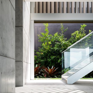 Design ideas for a contemporary staircase in Sydney with open risers and glass railing.
