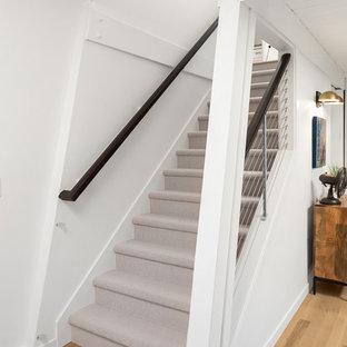 ポートランドの中サイズのカーペット敷きのおしゃれな直階段 (カーペット張りの蹴込み板、ワイヤーの手すり) の写真