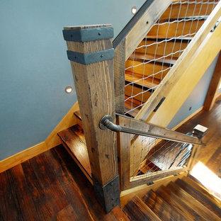 Idee per un'ampia scala a rampa dritta stile rurale con pedata in legno, alzata in legno e parapetto in materiali misti