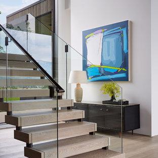 Inspiration pour un escalier sans contremarche design avec des marches en bois et un garde-corps en verre.