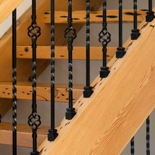 Foto di una grande scala a rampa dritta rustica con pedata in legno e nessuna alzata