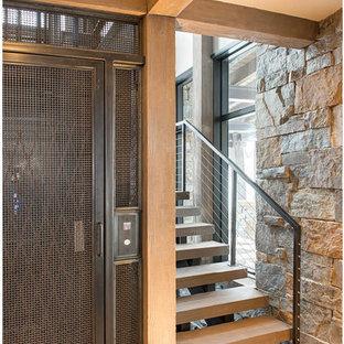 Réalisation d'un grand escalier sans contremarche flottant chalet avec des marches en bois et un garde-corps en câble.
