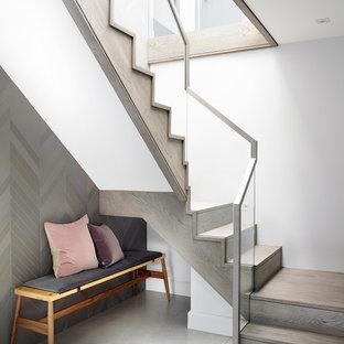 Diseño de escalera curva, contemporánea, grande, con escalones de madera, contrahuellas de vidrio y barandilla de metal