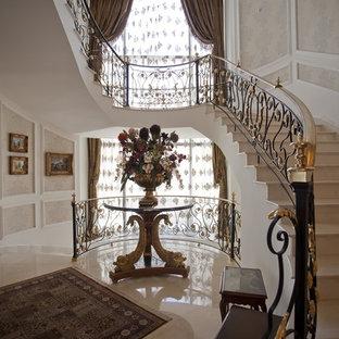 Idee per un'ampia scala curva vittoriana con pedata in marmo, alzata in marmo e parapetto in metallo