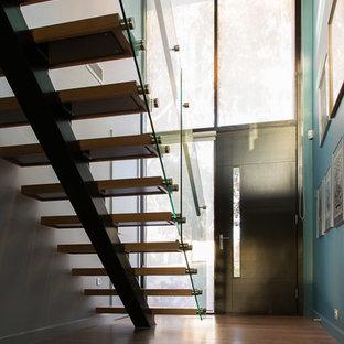 Ejemplo de escalera recta, contemporánea, de tamaño medio, con escalones de madera, contrahuellas de vidrio y barandilla de vidrio