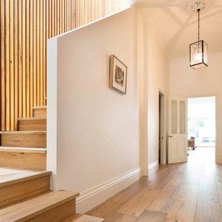 Ejemplo de escalera en L, contemporánea, grande, con escalones de madera y contrahuellas de madera