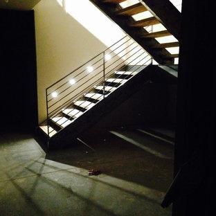 Cette image montre un grand escalier sans contremarche minimaliste en U avec des marches en bois.
