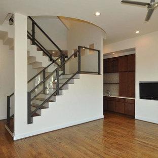 Exempel på en stor modern u-trappa i trä, med sättsteg i målat trä och räcke i glas
