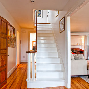 Staircase - traditional painted wood railing staircase idea in Boston with painted risers