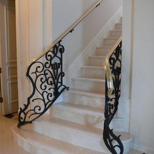 マイアミの中サイズの大理石の地中海スタイルのおしゃれな折り返し階段 (金属の手すり、大理石の蹴込み板) の写真