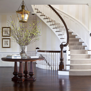 Large classic wood curved staircase in Boston with painted wood risers.