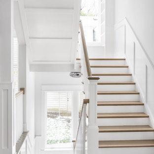 Источник вдохновения для домашнего уюта: п-образная лестница в стиле кантри с деревянными ступенями, крашенными деревянными подступенками, деревянными перилами и панелями на стенах