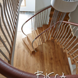 Staircase - mid-sized modern wooden curved staircase idea in London with wooden risers