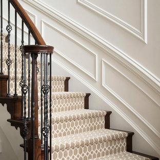 Réalisation d'un grand escalier courbe tradition avec des marches en moquette, des contremarches en moquette et un garde-corps en matériaux mixtes.