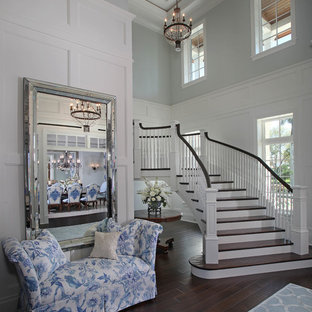 Huge island style wooden curved staircase photo in Miami
