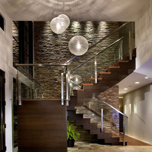 Design ideas for a contemporary wood glass railing staircase in Orlando.