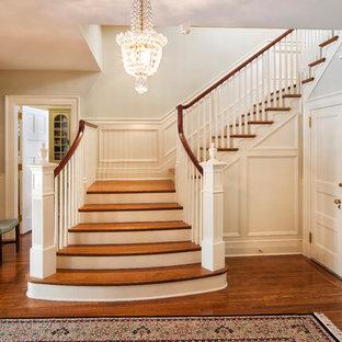 ニューヨークの巨大な木のトラディショナルスタイルのおしゃれな折り返し階段 (木の蹴込み板、木材の手すり) の写真
