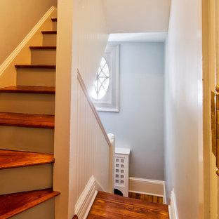 Ejemplo de escalera curva, tradicional, con escalones de madera, contrahuellas de madera y barandilla de madera