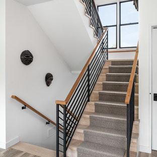 Ejemplo de escalera en U, de estilo de casa de campo, de tamaño medio, con escalones enmoquetados, contrahuellas enmoquetadas y barandilla de varios materiales
