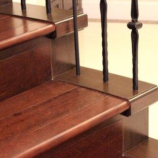 Foto di una scala a rampa dritta minimalista di medie dimensioni con pedata in legno, alzata in legno e parapetto in metallo