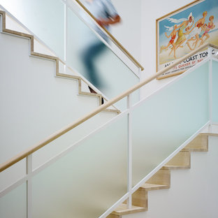 Inspiration for a coastal wooden u-shaped glass railing staircase remodel in Chicago with wooden risers