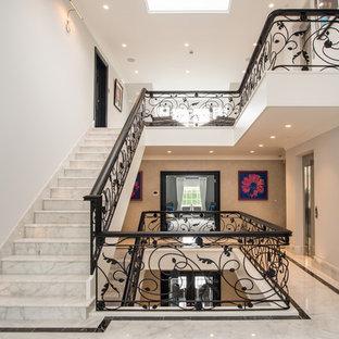 Aménagement d'un grand escalier droit contemporain avec des marches en marbre, des contremarches en marbre et un garde-corps en métal.
