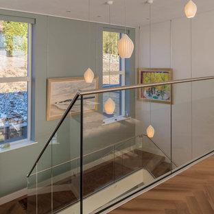 Idéer för att renovera en svängd trappa i trä, med sättsteg i glas och räcke i metall