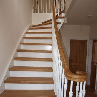 バッキンガムシャーの大きい木のカントリー風おしゃれなサーキュラー階段 (木の蹴込み板、木材の手すり) の写真