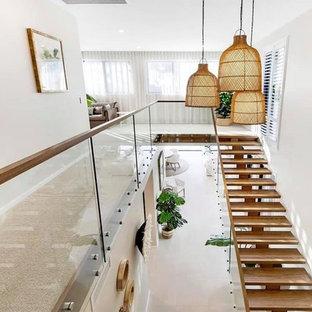 Idee per una grande scala a rampa dritta tropicale con pedata in legno e parapetto in vetro