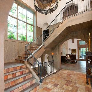 Diseño de escalera mediterránea con escalones de madera, contrahuellas de terracota y barandilla de metal