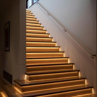 Imagen de escalera recta, actual, de tamaño medio, con escalones de madera, contrahuellas de madera y barandilla de metal
