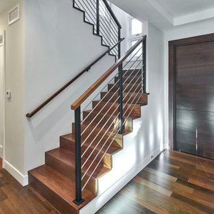 Ejemplo de escalera en U, clásica renovada, de tamaño medio, con escalones de madera, contrahuellas de madera y barandilla de varios materiales