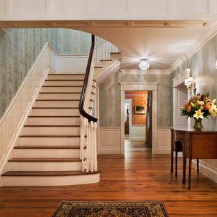 Modelo de escalera en L, tradicional, grande, con escalones de madera, contrahuellas de madera pintada y barandilla de madera