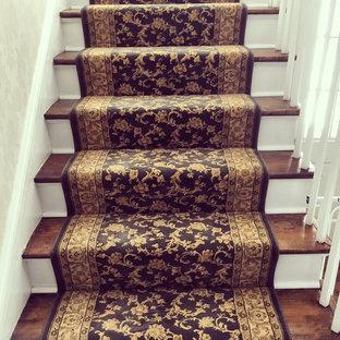 ニューヨークの中くらいの木のヴィクトリアン調のおしゃれな直階段 (フローリングの蹴込み板) の写真