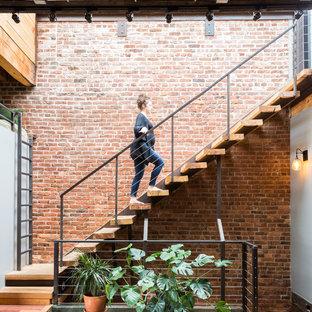 Ejemplo de escalera suspendida, industrial, sin contrahuella, con escalones de madera y barandilla de cable